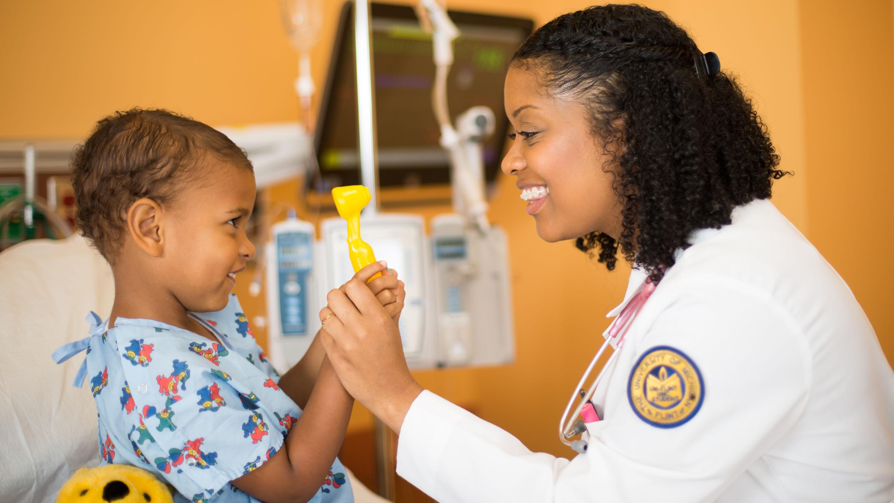 University of Michigan-Flint nursing student treating a pediatric patient