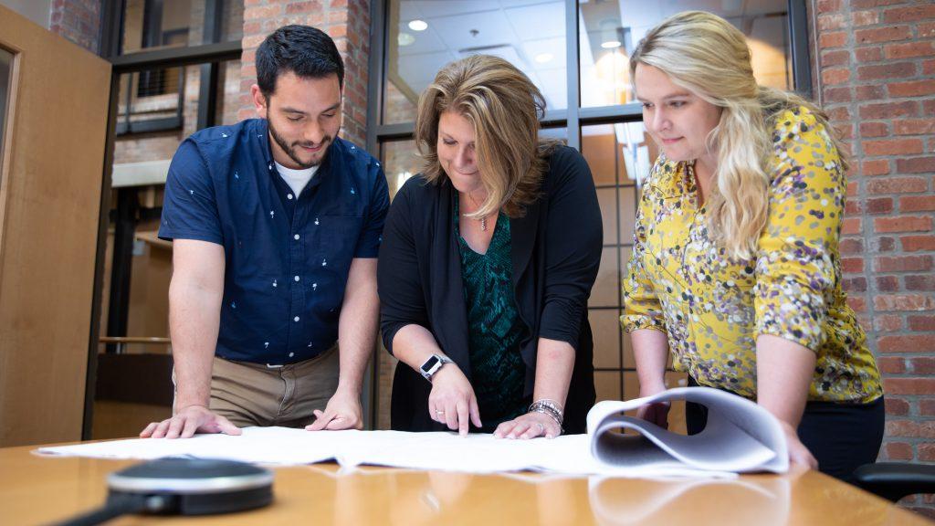 ROWE CEO Leanne Panduren reviewing blueprints with ROWE staff