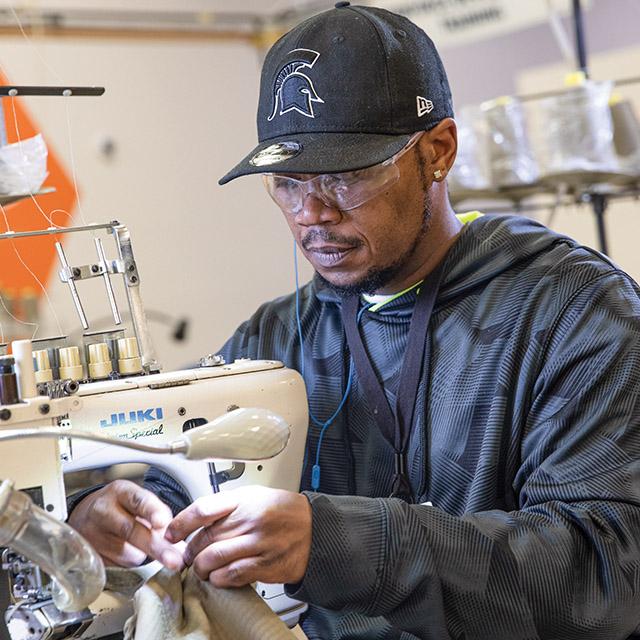 Production floor employee sews garments at Peckham Inc.