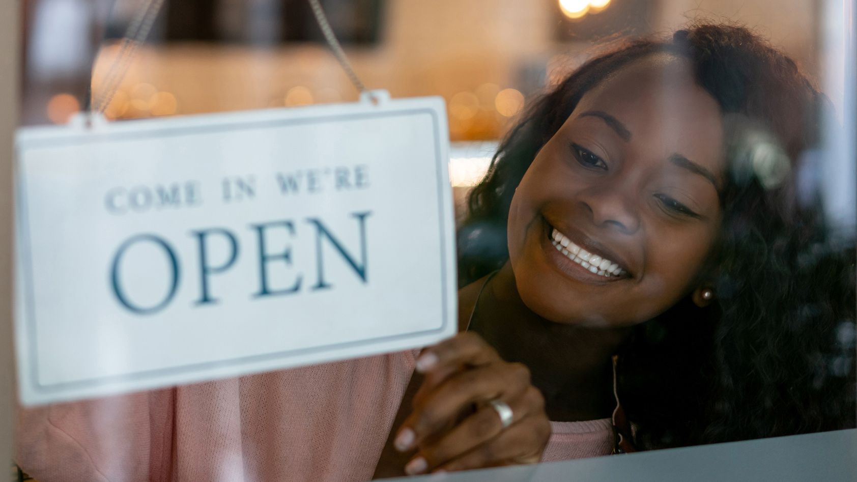 """A young woman places """"come in we're open"""" sign in her business window"""